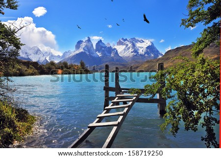 Picturesque little island in the lake Pehoe. For light boats on the shore of the island constructed pier. On the other side of the lake clouds cover the cliffs of Los Kuernos - stock photo