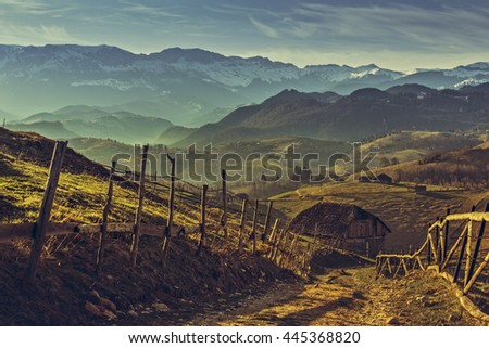 Picturesque morning rural scenery with traditional Romanian wooden house and country road uphill in Sirnea village, Brasov county, Romania. Travel destinations. - stock photo