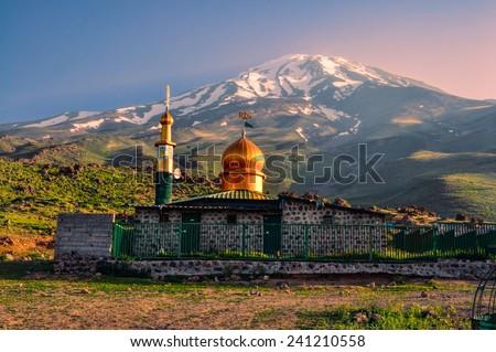 Picturesque mosque underneath volcano Damavand, highest peak in Iran - stock photo