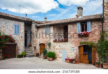 picturesque old court yard decorated with flowers in a small town in Italy - stock photo