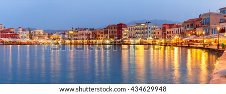 Picturesque panoramic view of old harbour and Venetian quay of Chania during twilight blue hour, Crete, Greece