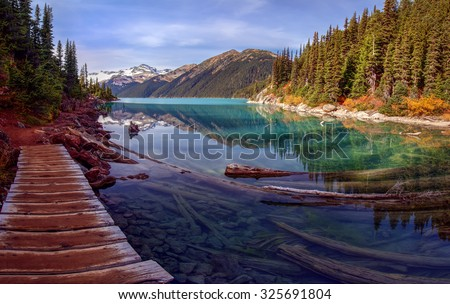 Picturesque path along turquoise mountain lake with a pine tree lined shore and snow capped mountains in the background - stock photo