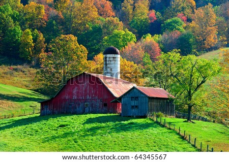 picturesque red barn in front of beautiful autumn fall colorful trees - stock photo