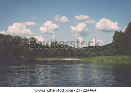 Picturesque river view with clouds and trees in the background - retro, vintage style look - stock photo