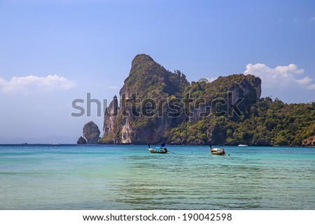 Picturesque rocks at the seashore and longtail boats in Phi-Phi Islands, Thailand - stock photo