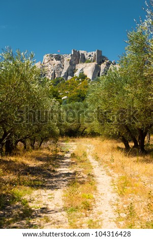 Picturesque rural dirt road leads to the historic Chateau Des Baux, a castle ruins atop a scenic rocky mountain on a clear sunny, blue sky day in Les Baux de Provence in France. Vertical copy space - stock photo