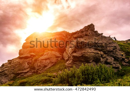 Picturesque scenery of Carpathian mountains, sun over stone, evening time