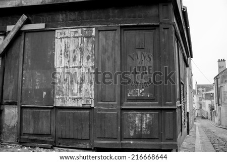 Picturesque streets of medieval city Pontoise (France). Closed abandoned wine shop. Perfect place for historic films shooting. Aged photo. Black and white. - stock photo