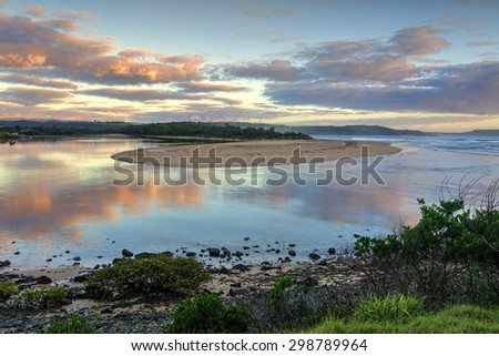 Picturesque sunrise as Minamurra river meets the ocean entrance and reflections in its waters.  South Coast NSW Austtralia. - stock photo