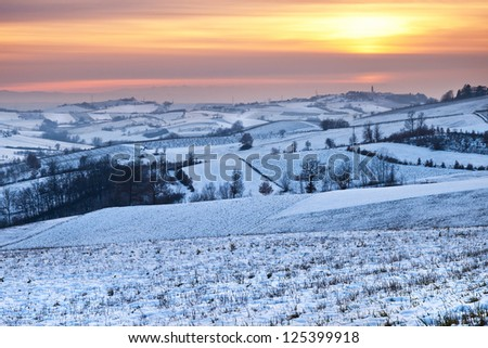 Picturesque sunset in piedmont hillside landscape covered with snow - stock photo
