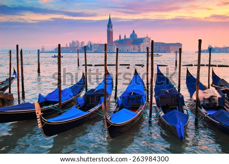 Picturesque view of blue gondolas in the night in Venice, Italy. - stock photo