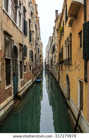 Picturesque view of Gondolas on lateral narrow Canal on a foggy day, Venice, Italy.