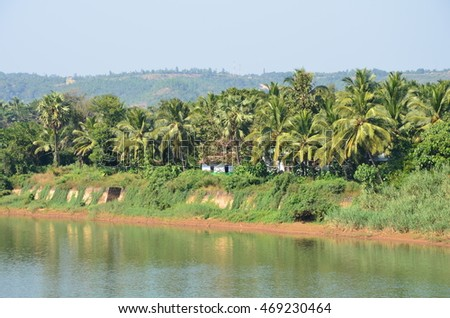 Picturesque view of Phalguni River with hills and Coconut Palms in the background at Polali, Addur, Mangalore, Karnataka, India