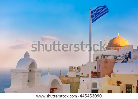 Picturesque view of white houses, church and Greek flag in the morning, Oia or Ia, island Santorini, Greece - stock photo
