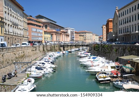Picturesque view on boats in city channel in Livorno, Italy - stock photo