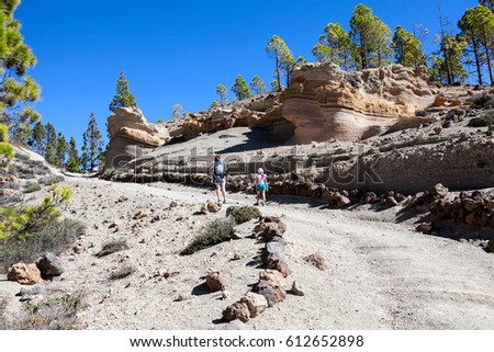 Picturesque volcanic rocks are on footpath to the Lunar landscape. A woman with her daughter hiking on a mountain path. Tenerife, Canary Islands, Spain