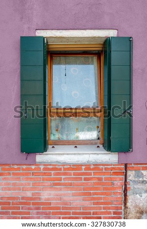 Picturesque window with green shutters on purple and red bricks wall of houses on the famous island Burano, Venice, Italy