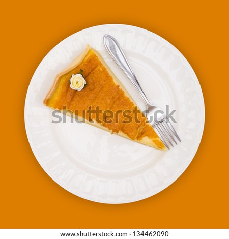 Pie decorated with flower candy on white plate with fork against orange background, overhead view