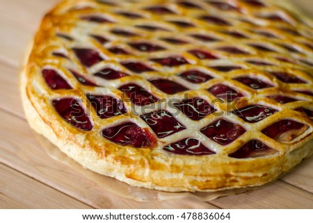 Pie on wooden surface. Dough with berries. Freshly cooked cherry pie. Tasty and nutricious dessert.