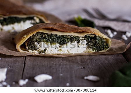 Pie or strudel with spinach and feta cheese - stock photo