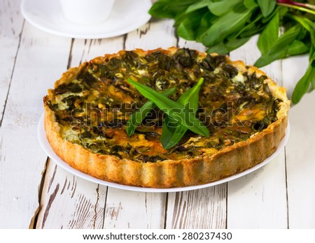 pie with a ramson on a white wooden background - stock photo