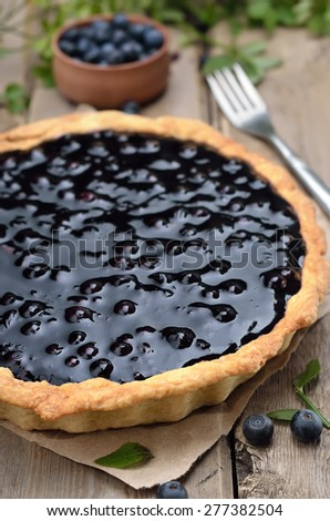 Pie with blueberries on rustic wooden table, close up - stock photo