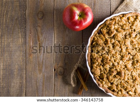 Pie with crumble on plank background. Apple crumble. Apple pie with crumble on wooden background.  - stock photo