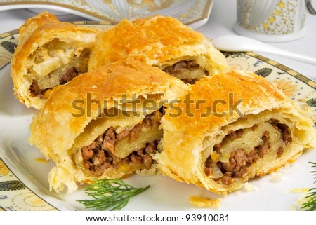 pie with ground beef filling, rolls of  puff pastry with meat on plate - stock photo