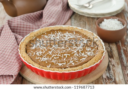 Pie with pumpkin and chocolate in ceramic form on a wooden table