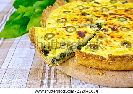 Pie with spinach, cheese and olives on a round board, spinach leaves on a background of a linen tablecloth - stock photo