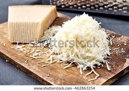 Piece and grated parmigiano reggiano or parmesan cheese on wwood board on checkered napkin . Grated parmesan uses in pasta dishes, soups, risottos and grated over salads.