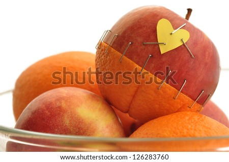 piece of an apple and a orange stapled together - stock photo