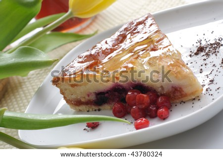 piece of an apple pie with red berries on a white plate