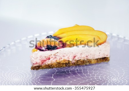 Piece of an unbaked fruit cake with cream on a openwork plate