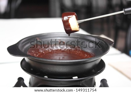 piece of banana dipped into a chocolate fondue - stock photo