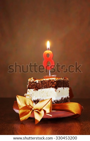 Piece of Birthday Chocolate Cake with Burning Candle as a Number Eight on Brown Background - stock photo