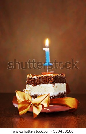 Piece of Birthday Chocolate Cake with Burning Candle as a Number One on Brown Background - stock photo