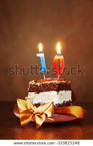 Piece of Birthday Chocolate Cake with Burning Candle as a Number Ten on Brown Background - stock photo
