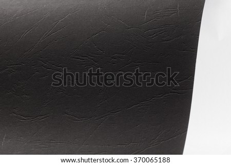 Piece of black texture cardboard on gray background - stock photo