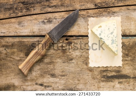 Piece of blue cheese with knife on wood background. Top view image cheese with mold on old paper - stock photo