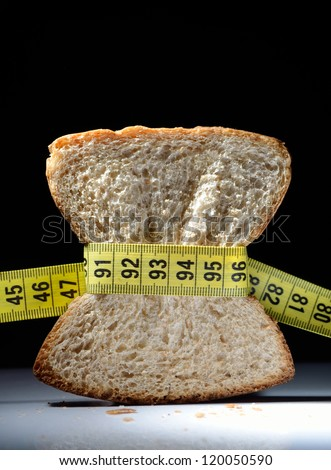 Piece of bread grasped by measuring tape with dark background - stock photo
