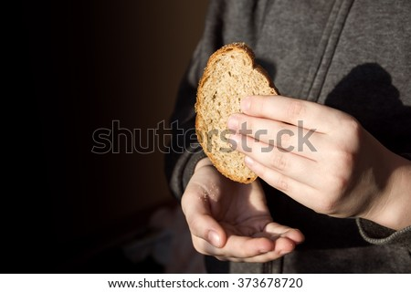 Piece of bread in children hands. Hunger and helping concept. - stock photo