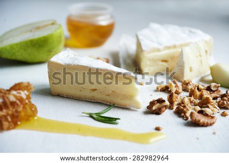 piece of brie, pear and walnuts over white - stock photo