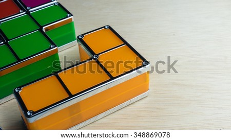 Piece of bright colored square blocks puzzle geometric shaped cube on wooden surface. Concept of design construction or creative problem solving. Slightly de-focused and close-up shot. Copy space. - stock photo