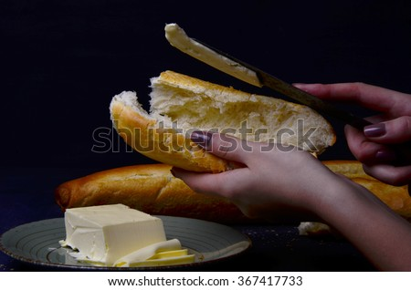 piece of butter, fresh bread and a knife