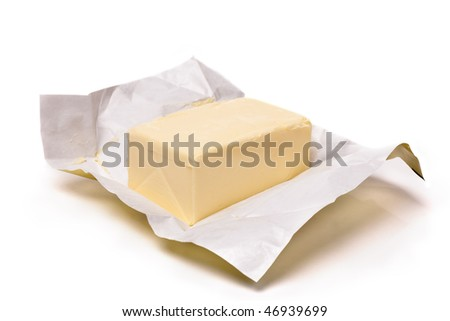 Piece of butter in paper on a white background. Shallow focus - stock photo