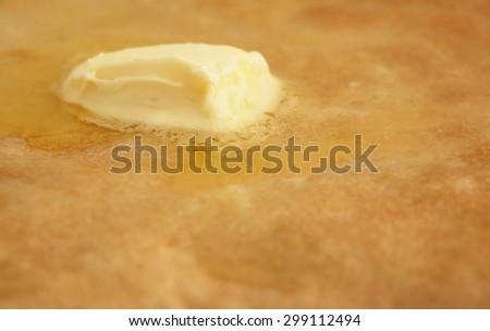 piece of butter melting on the surface of a hot pancake - stock photo