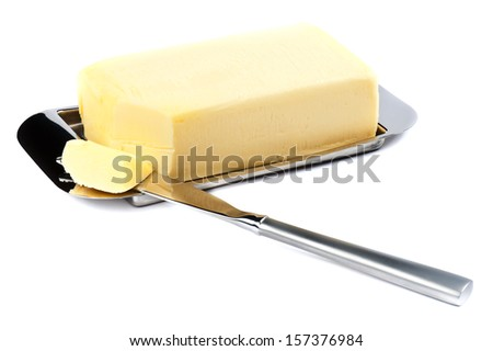 Piece of Butter on Silver Plate with Knife. - stock photo