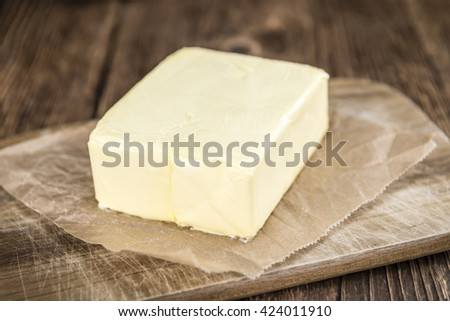Piece of Butter on wooden background (selective focus; close-up shot) - stock photo