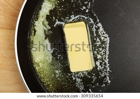 piece of butter while melting in frying pan - stock photo